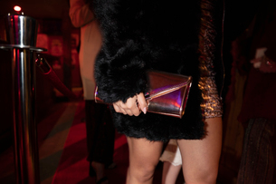 Close up young woman holding clutch purse in nightclub queueの写真素材 [FYI02337762]
