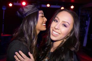 Portrait happy women friends hugging in nightclubの写真素材 [FYI02337765]