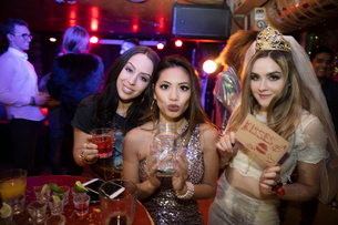 Portrait confident bachelorette and friends with kissing sign and jar in nightclubの写真素材 [FYI02337781]