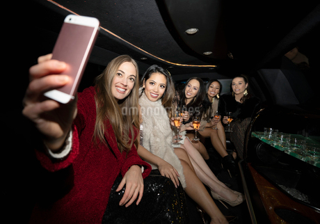 Women friends drinking champagne and taking selfie in limousineの写真素材 [FYI02337814]