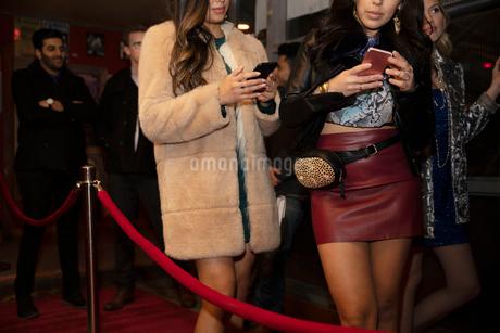 Young women using smart phones, waiting in nightclub queueの写真素材 [FYI02337815]