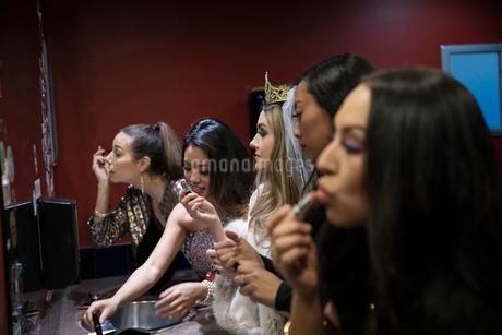 Bachelorette and friends applying makeup in nightclub bathroom mirrorの写真素材 [FYI02337825]