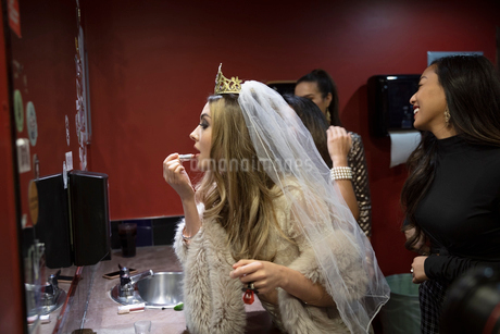 Bachelorette applying lipstick in nightclub bathroom mirrorの写真素材 [FYI02337852]