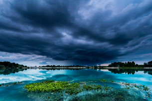 Storm clouds over a quarry lake with water plants, nearの写真素材 [FYI02337962]