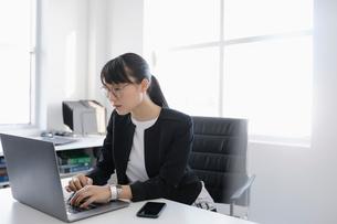 Focused businesswoman using laptop in officeの写真素材 [FYI02338049]