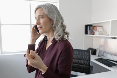 Businesswoman talking on cell phone in officeの写真素材 [FYI02338131]
