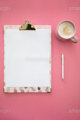 View from above clipboard and coffee on pink backgroundの写真素材 [FYI02338161]