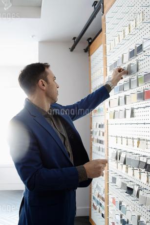 Male interior designer looking at swatches in design studioの写真素材 [FYI02338197]
