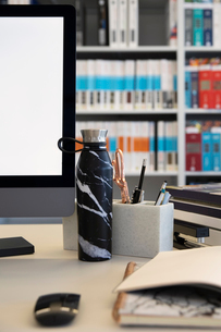 Water bottle on desk next to computer in officeの写真素材 [FYI02338217]