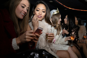 Bachelorette and friends drinking champagne in limousineの写真素材 [FYI02338221]