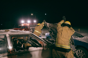 Firefighters tending to  burned car at scene of car accidentの写真素材 [FYI02338225]