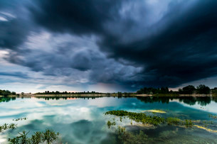 Storm clouds over a quarry lake with water plants, nearの写真素材 [FYI02338228]