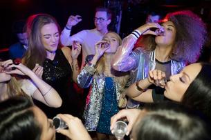 Women taking tequila shots in nightclubの写真素材 [FYI02338267]