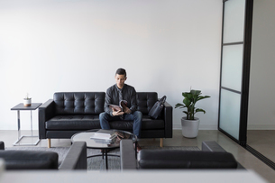 Businessman waiting, reading magazine on leather sofa in office lobbyの写真素材 [FYI02338269]
