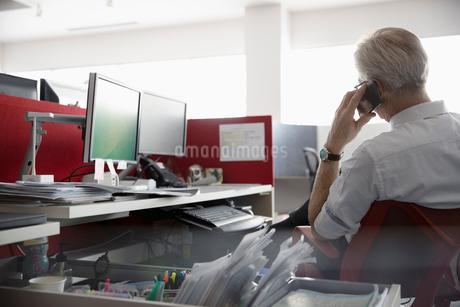 Businessman talking on smart phone at deskの写真素材 [FYI02338326]
