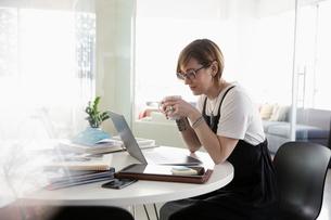Businesswoman drinking coffee, working at laptopの写真素材 [FYI02338328]