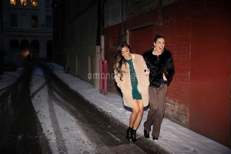 Women friends leaving nightclub, walking on snowy urban streetの写真素材 [FYI02338423]