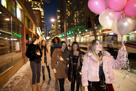 Bachelorette and friends with balloons on snowy urban sidewalkの写真素材 [FYI02338481]