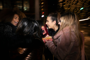 Women friends eating hot dogs on urban street at nightの写真素材 [FYI02338494]