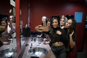 Bachelorette and friends taking selfie in nightclub bathroomの写真素材 [FYI02338517]