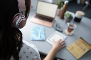 Businesswoman with headphones using digital tablet at deskの写真素材 [FYI02338560]