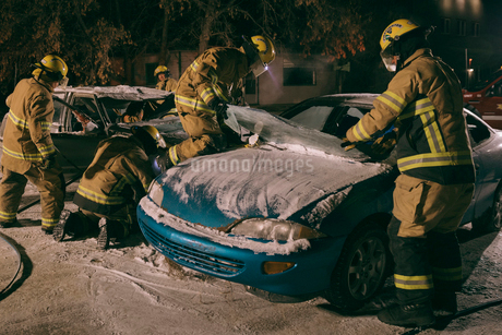 Firefighters tending to burnt car at scene of car accidentの写真素材 [FYI02338649]