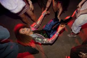 Laughing young woman falling on dance floor in nightclubの写真素材 [FYI02338653]