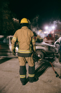 Firefighters extinguishing car fire at scene of car accidentの写真素材 [FYI02338737]
