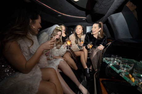 Bachelorette and friends drinking champagne in limousineの写真素材 [FYI02338771]