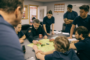 Firefighters meeting around map in fire stationの写真素材 [FYI02338782]