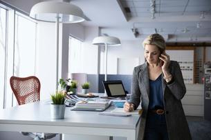 Female interior designer talking on smart phone in officeの写真素材 [FYI02338802]