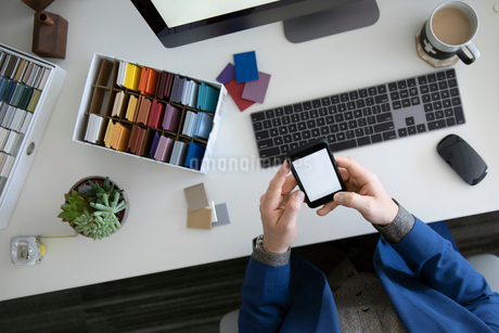 View from above interior designer using smart phone at deskの写真素材 [FYI02338813]