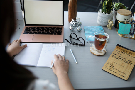 Businesswoman writing in journal at laptopの写真素材 [FYI02338860]