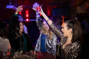 Exuberant young women friends toasting cocktails in nightclubの写真素材 [FYI02338924]