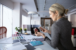 Female interior designer reviewing swatches in design studioの写真素材 [FYI02339020]
