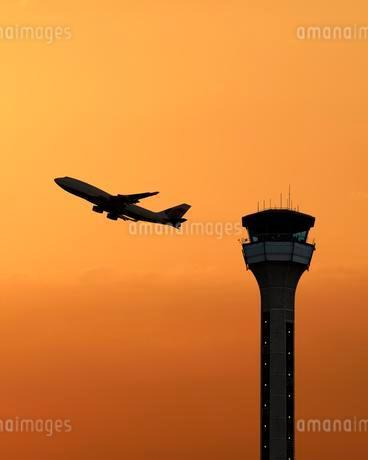 Air traffic control tower with a plane taking off atの写真素材 [FYI02339387]
