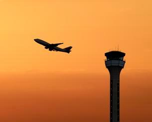 Air traffic control tower with a plane taking off atの写真素材 [FYI02339755]