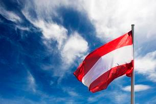 Flag of Austria against blue sky with white cloudsの写真素材 [FYI02339874]