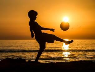 Boy with soccer ball, sunset at the sea, beach, Italyの写真素材 [FYI02339878]