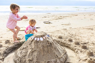 Two girls, toddlers, playing with a sand castle on theの写真素材 [FYI02339996]