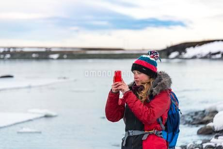 Young woman taking photo with mobile phone, Fjallsarlonの写真素材 [FYI02340023]
