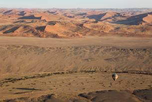 Hot-air balloon above an arid plain and the dry riverbed ofの写真素材 [FYI02340067]