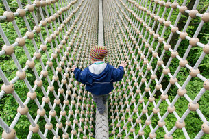 Toddler, 3 years, walking over a secured rope aboveの写真素材 [FYI02340222]