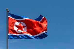 North Korea flag blowing in the wind, blue skyの写真素材 [FYI02340275]