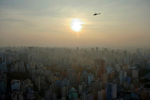Helicopter above a cityscape with skyscrapers at sunsetの写真素材 [FYI02340440]