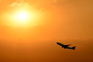 Airplane taking off silhouetted against a sunsetの写真素材 [FYI02340449]