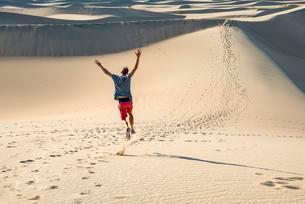 Young man, tourist running down sand dune, Mesquite Flatの写真素材 [FYI02340451]