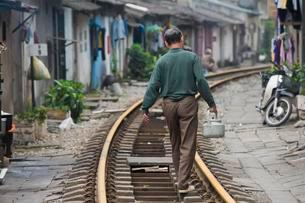 Man with kettle walking on Railway Track, living next toの写真素材 [FYI02340500]
