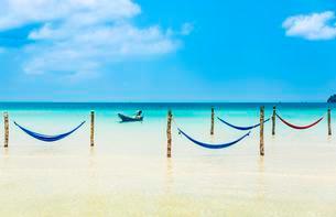 Motorboat, hammocks on idyllic sandy beach, turquoise seaの写真素材 [FYI02340594]