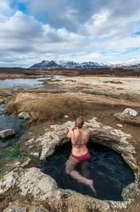 Young woman in hot spring looking towards mountains, Eyjarの写真素材 [FYI02340645]